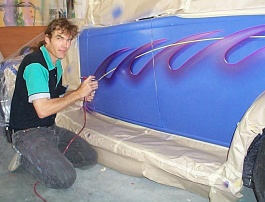 Picture of Hans Kreuzen airbrushing artwork onto a Hotrod